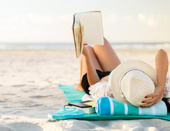 A woman reads a book on the beach